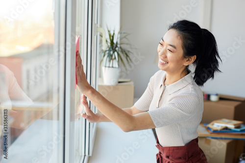 Obraz na płótnie Waist up portrait of young Asian woman washing windows while enjoying Spring cle
