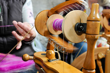 A Woman Spins Wool Using A Traditional Spinning Wheel.