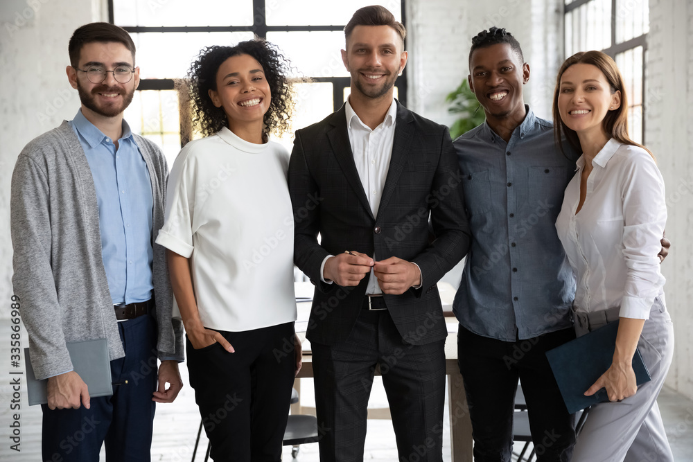 Fototapeta Portrait of standing in row smiling diverse team looking at camera. Happy multiethnic corporate staff, young specialists, company representatives, bank workers photo shoot, HR agency recruitments.