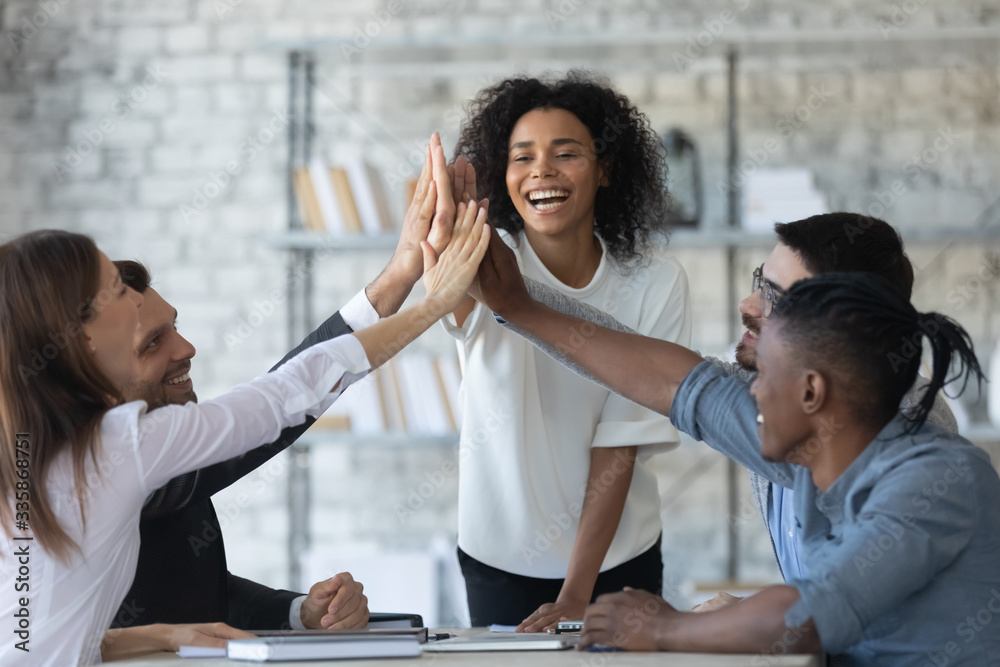 Fototapeta Excited successful african american businesswoman with multiracial business people giving high five, celebrating win. Happy employees team engaged in team building activity at corporate meeting.