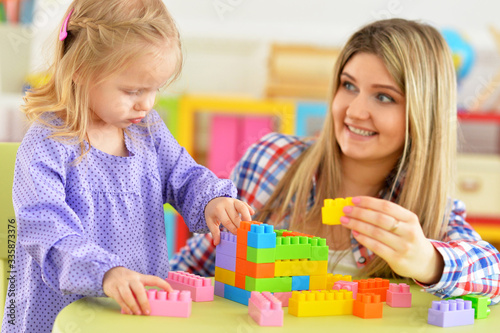 Cute little girl and her mother playing colorful plastic blocks
