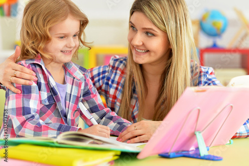 Mother and daughter doing homework together in room