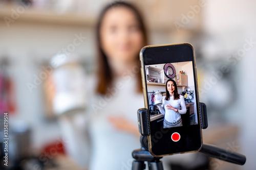 Fototapeta ragazza fa un tutorial di cucina con il suo cellulare obraz