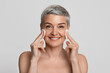 Beautiful middle aged woman cleansing skin on face with cotton pads