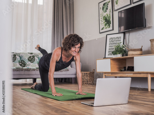 Fototapeta happy and smiling women looking into the laptop in doing a fitness pilates workout in her living room at home obraz