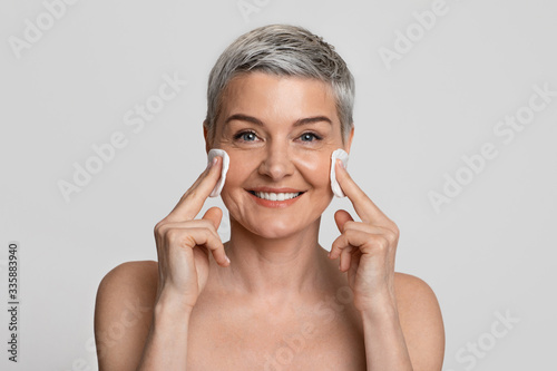 Fototapeta Beautiful middle aged woman cleansing skin on face with cotton pads