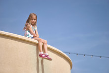 Little Girl Sits On The Edge O...