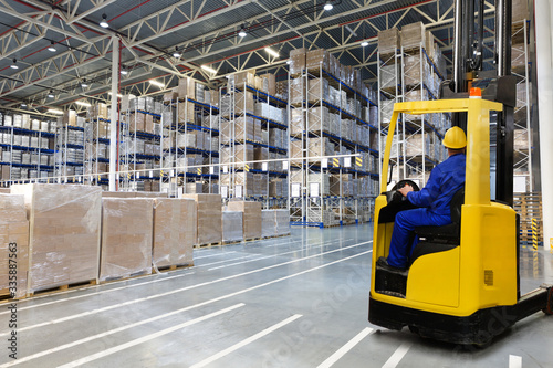 Fotomural Huge distribution warehouse with high empty shelves and forklift with driver in yellow helmet