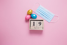 Wooden Cube With The Date Of The Celebration Of Easter On April 19. Medical Mask Ban On Mass Celebrations. Easter Eggs On A Pink Background. COVID-19.