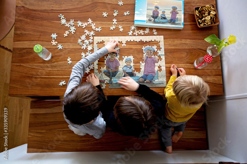 Fototapeta Three children, boys, assembling puzzle with their picture from the beach, playing at home obraz