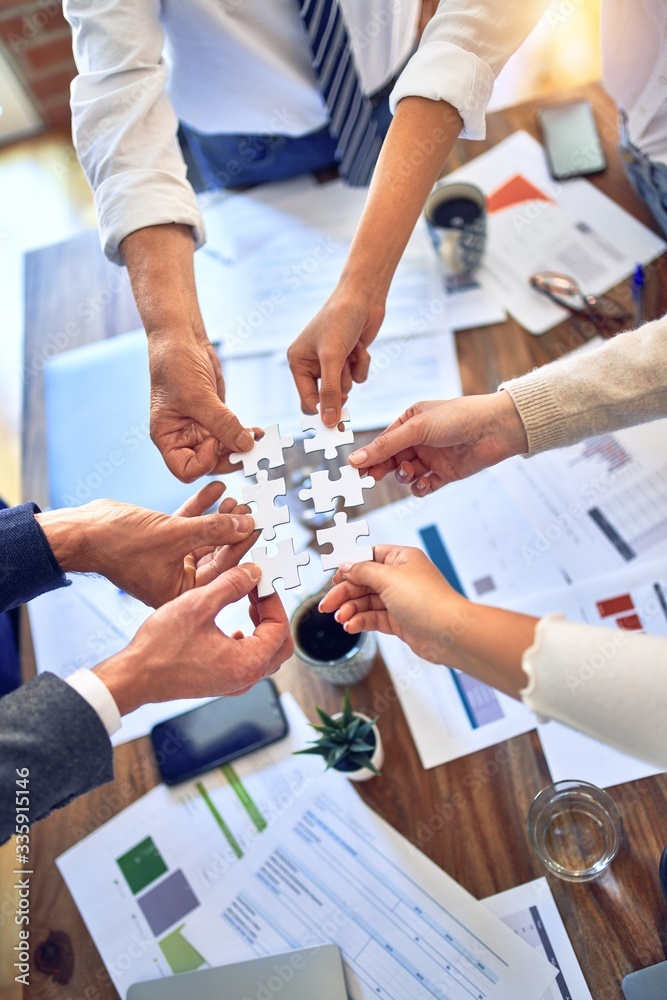 Fototapeta Group of business workers with hands together connecting pieces of puzzle at the office