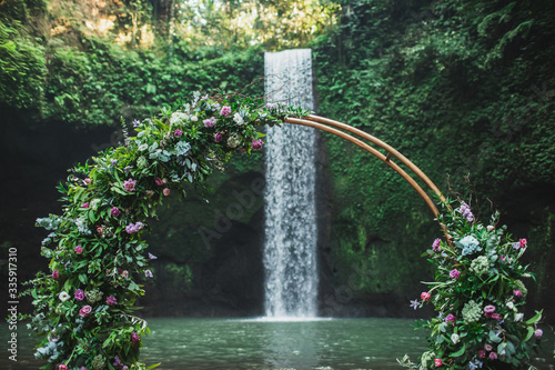 Photo Round bronze wedding arch decorated with pink roses and greens