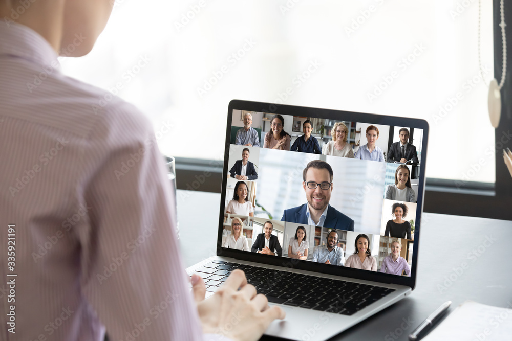 Fototapeta Multiracial people involved in group video call using modern tech videoconferencing application for study or business concept, view over businesswoman shoulder sitting at desk working with colleagues