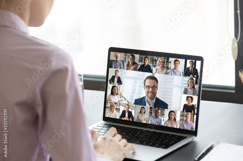 Multiracial people involved in group video call using modern tech videoconferencing application for study or business concept, view over businesswoman shoulder sitting at desk working with colleagues - 335921191