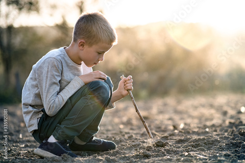 Fototapeta Child boy playing with wooden stick digging in black dirt ground outdoors. obraz