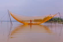 A Traditional Fisherman Under His Nets On The Thu Bon River, Hoi An, Vietnam At Dawn