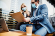 Smiling female in a face mask scrutinizing a contract