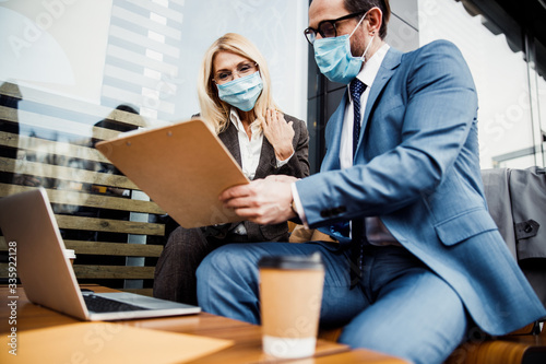 Fotografia Smiling female in a face mask scrutinizing a contract