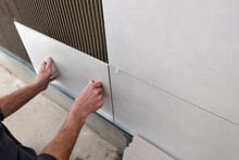 Worker Hands Putting Ceramic Tiles On The Wall.