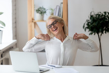 Happy 60 Years Old Businesswoman With Hands Behind Head Relaxing In Comfortable Office Chair During Break. Smiling Female Employee With Closed Eyes Resting After Work Done, Leaning Back.