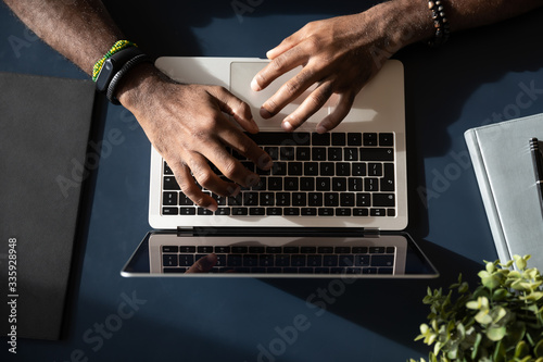 Close up top view of African American male worker busy typing on laptop keyboard at office workplace, biracial man employee text on modern computer gadget, consult client online, technology concept