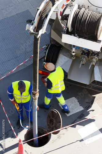 sewerage truck service and utility workers for cleaning sewer pipes in city street Wall mural