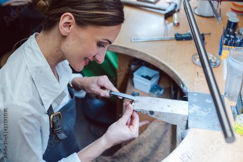 Obraz na plátně Jeweler working with tools on a piece of jewelry