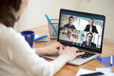 Diverse people take part in group video call pc screen cam app view over woman shoulder, seated at desk. Solve business issues distantly during coronavirus pandemic outbreak, videoconferencing concept - 335932703