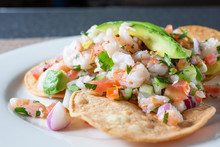 A Closeup View Of A Plate Of Shrimp Tostada, In A Restaurant Or Kitchen Setting.