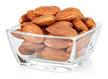 Almond Nuts In A Small Transparent Glass Square Bowl Isolated On White Background