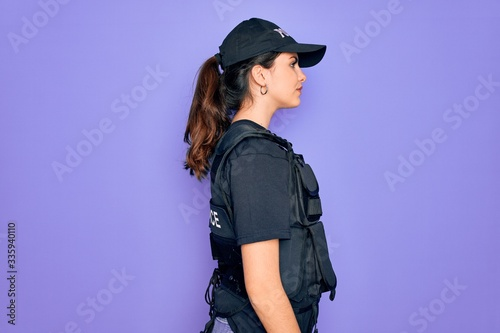 Young police woman wearing security bulletproof vest uniform over purple background looking to side, relax profile pose with natural face and confident smile Fotobehang