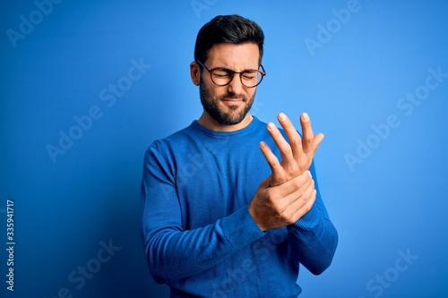 Young handsome man with beard wearing casual sweater and glasses over blue backg Wallpaper Mural