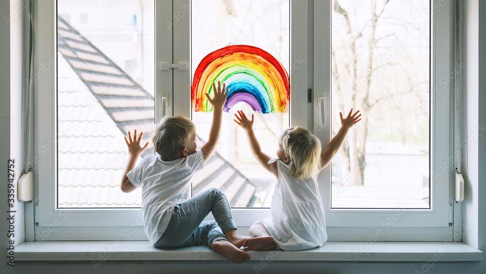 Fototapeta Little children on background of painting rainbow on window