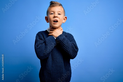 Fototapeta Young little caucasian kid with blue eyes wearing winter sweater over blue background shouting and suffocate because painful strangle