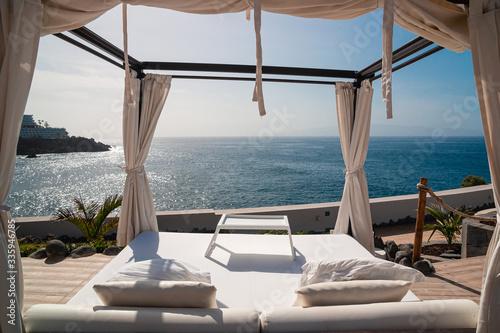 Fototapeta Sunbathing bed in a luxury pool hotel with stunning ocean views