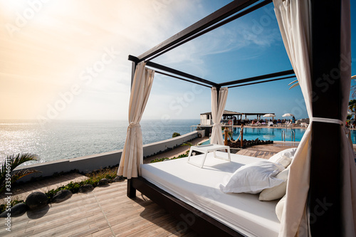 Valokuva Sunbathing bed in a luxury pool hotel with stunning ocean views