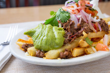 A View Of A Plate Of Carne Asada Fries, In A Restaurant Or Kitchen Setting.