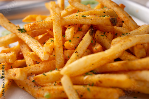 Obraz na płótnie A closeup view of a tray of cajun style french fries in a restaurant or kitchen setting