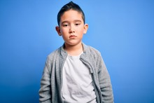 Young Little Boy Kid Wearing Sport Sweatshirt Over Blue Isolated Background With Serious Expression On Face. Simple And Natural Looking At The Camera.