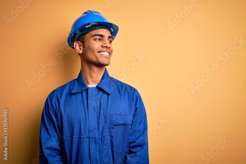 Vászonkép Young handsome african american worker man wearing blue uniform and security helmet looking away to side with smile on face, natural expression