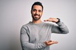 canvas print picture - Young handsome man with beard wearing casual sweater standing over white background gesturing with hands showing big and large size sign, measure symbol. Smiling looking at the camera. Measuring