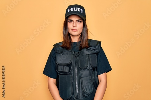 Fotografia, Obraz Young beautiful brunette policewoman wearing police uniform bulletproof and cap skeptic and nervous, frowning upset because of problem