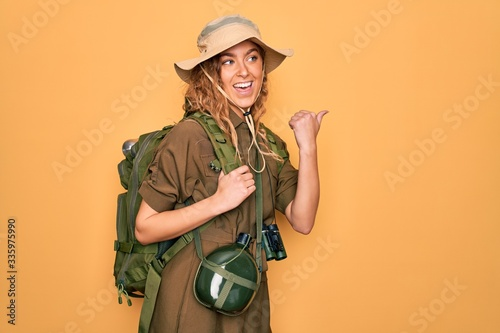 Fototapeta Young blonde explorer woman with blue eyes hiking wearing backpack and water canteen smiling with happy face looking and pointing to the side with thumb up