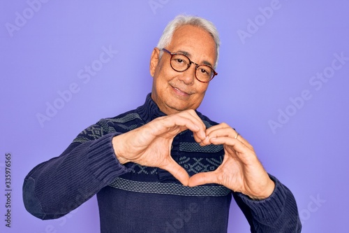 Cuadros en Lienzo Middle age senior grey-haired man wearing glasses and winter sweater over purple background smiling in love doing heart symbol shape with hands
