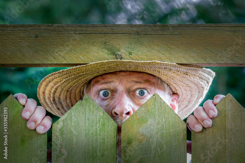 Fotomural An elderly man in a straw hat looks curiously over a garden fence