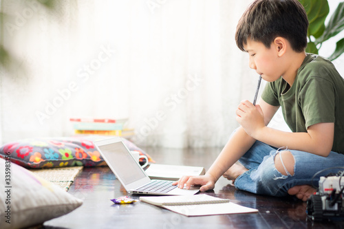 Leinwand Poster Smart looking Asian preteen boy sit crossed legs, holding pen against his lips,