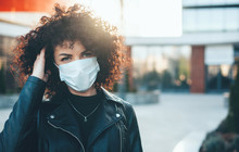 Young Caucasian Woman With Curly Hair And Black Leather Jacket Is Wearing Protective Mask