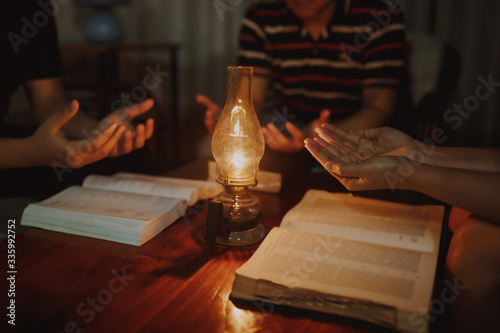 Valokuvatapetti Christian family worship God in a home over the holy bible and vintage lamp on w