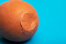 Brown Cracked Egg On A Blue Ba...