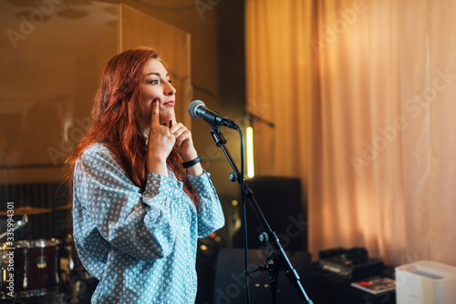 Fotografía girl does exercises with lips at chants in vocal lesson near the microphone